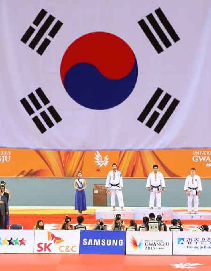 The Korean national flag is hoisted at the judo winners' ceremony as gold medalist Cho Gu-ham, second from right, stands on the podium at the Yeomju Bitgoeul Gymnasium in Gwangju, Saturday. / Yonhap