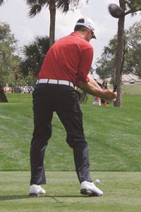 At the top, this tour player's right elbow is high and far away from the right hip; you can see only three of his belt loops. As you start the downswing, if you drop the right elbow but don't tuck it, you should see more than three belt loops because the righthip comes out to meet the elbow.It sure looks like this player has tucked his elbow into his hip, but actually, his hip has come out to meet the elbow - a big difference. Note how upright his spine is, even though the club has not been released yet. If he had tucked his elbow, his spine would be tilted incorrectly, away from the target.
