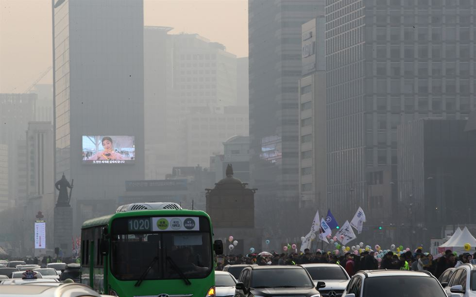 People walk in the rain in a fog-shrouded Gwanghwamun Square on Sunday. / Yonhap