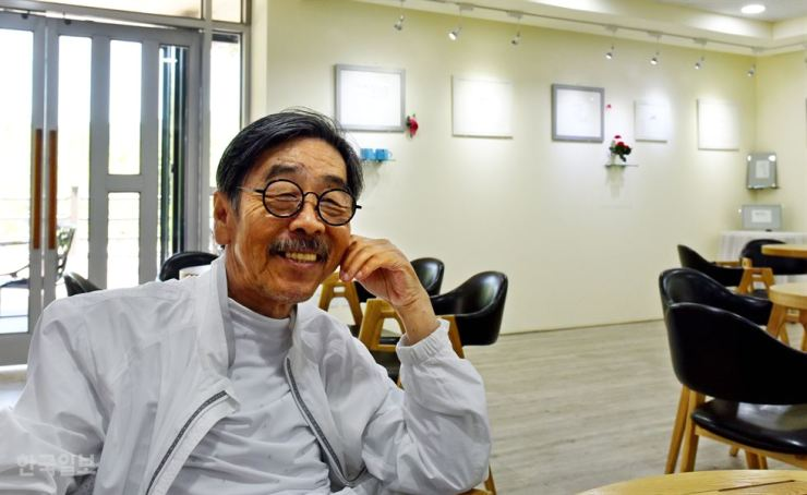 Novelist and artist Lee Oi-soo smiles at a facility in Gamseong Village in the county of Hwacheon, Gangwon Province, in this June 6, 2017, file photo. Lee has lived in housing in the park for a decade and is under pressure to leave the facility. / Korea Times