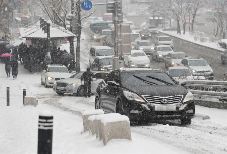 A driver puts chains on the tires of his car in the middle of a road leading from southwestern Seoul to Gwacheon in Gyeonggi Province on Monday, when heavy snow advisories were issued for Seoul and nearby cities. / Yonhap