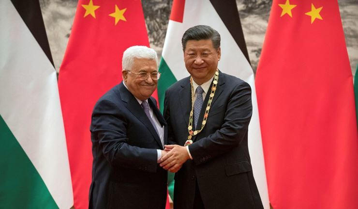 Palestinian President Mahmoud Abbas, left, shakes hands after presenting a medallion to Chinese President Xi Jinping, right, during a signing ceremony at the Great Hall of the People in Beijing, China, July 18, 2017.