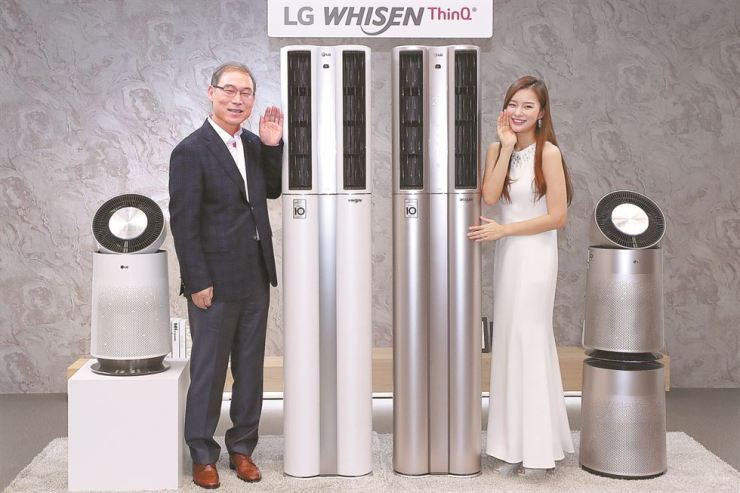 Song Dae-hyun, left, president of LG Electronics' home appliance and air systems business, poses next to the LG Whisen ThinQ, the firm's new air conditioner outfitted with artificial intelligence technology, ahead of a launch event at LG's head office on Yeouido, Seoul, Thursday. / Yonhap
