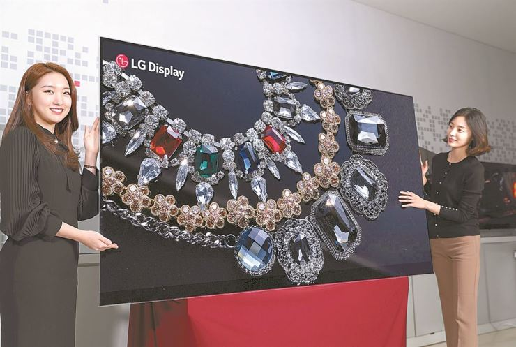 Models show off LG Display's 88-inch 8K OLED display, both the largest and the highest-resolution OLED panel to date. The company plans to display the technology at the Consumer Electronics Show (CES), scheduled for Jan. 9 to 12 in Las Vegas. Courtesy of LG Display