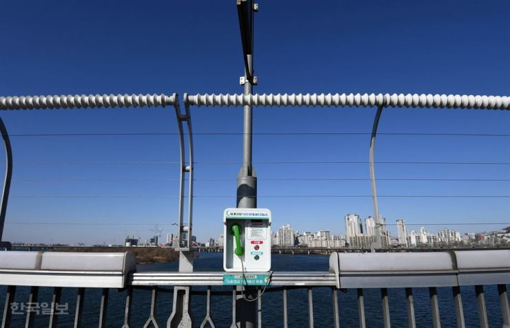 A phone and fence on the Mapo Bridge in Seoul aim to prevent suicide. The phone directly connects the caller to an expert in suicide prevention. / Korea Times photo by Suh Jae-hoon.
