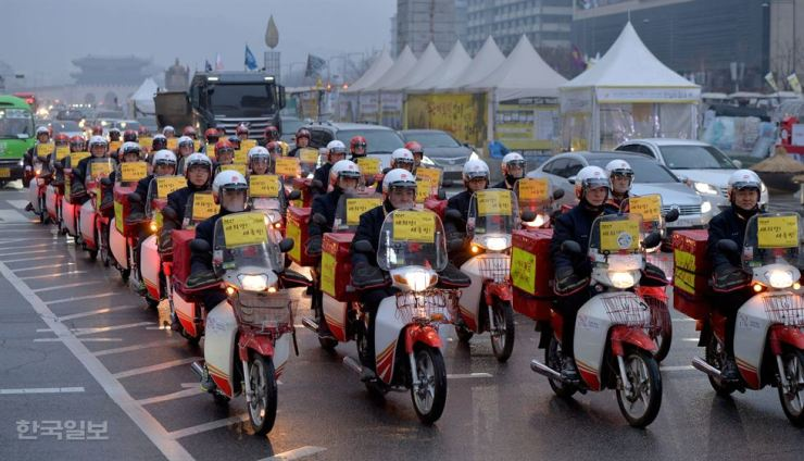 Gwanghwamun Post Office workers parade on their mopeds on Sejongdaero Road in Seoul's Gwanghwamun Square on Jan. 2, 2017, as they start their first working day of the year. / Korea Times file