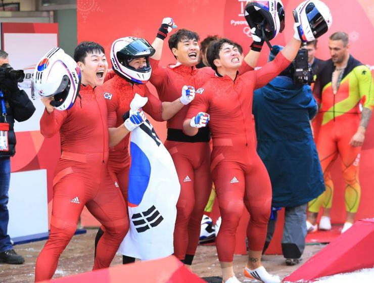 South Korea's four man bobsleigh team Won Yun-jong (left), Seo Young-woo, Kim Dong-hyun, and Jun Jung-lin celebrating after winning silver at the PyeongChang Sliding Center Sunday. / Yonhap