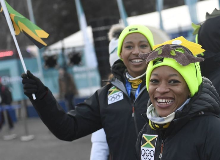 Jazmine Fenlator-Victorian, left, and Audra Segree of the Jamaican bobsled team react during the official team welcoming ceremony at the PyeongChang Olympic Village, Feb. 7. Yonhap