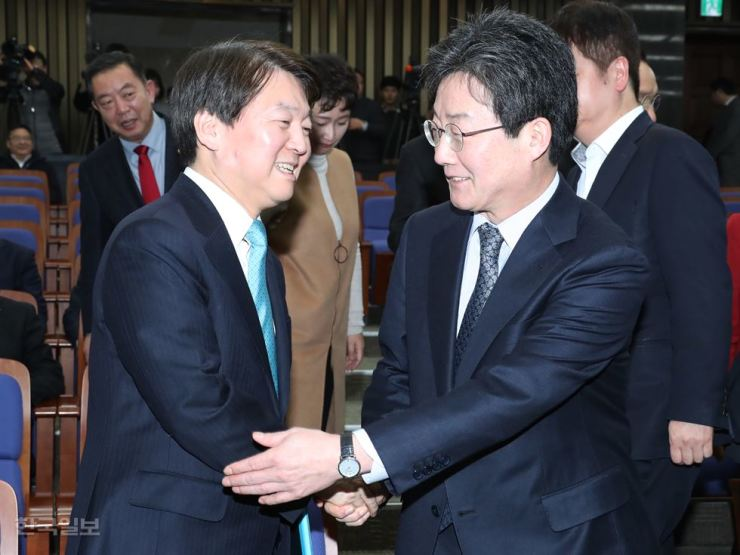 People's Party Chairman Ahn Cheol-soo, left, and Bareun Party Chairman Yoo Seong-min shake hands at a meeting in the National Assembly, Monday. / Korea Times photo by Oh Dae-geun