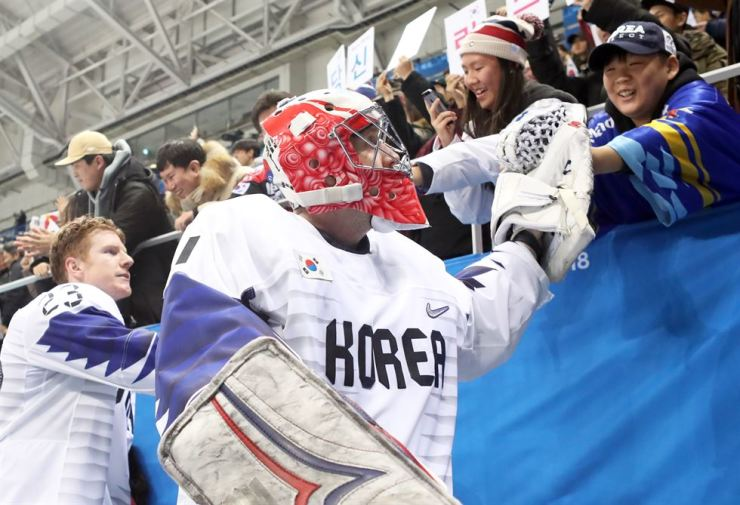 Men's ice hockey team goalie Matt Dalton, right, shakes hands with cheering fans after the preliminary round game against Canada at Gangneung Hockey Center, Sunday. / Yonhap