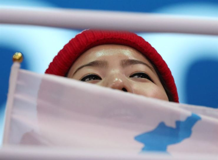 A North Korean cheerleader chants for Team Korea with a unification flag featuring a blue image of the Korean Peninsula with a blue dot, during the women's ice hockey match against Switzerland at the Gwandong Ice Hockey Center in the eastern city of Gangneung, Saturday. The IOC banned the flag for violating its rule on political statements. / Korea Times photo by Shim Hyun-chul