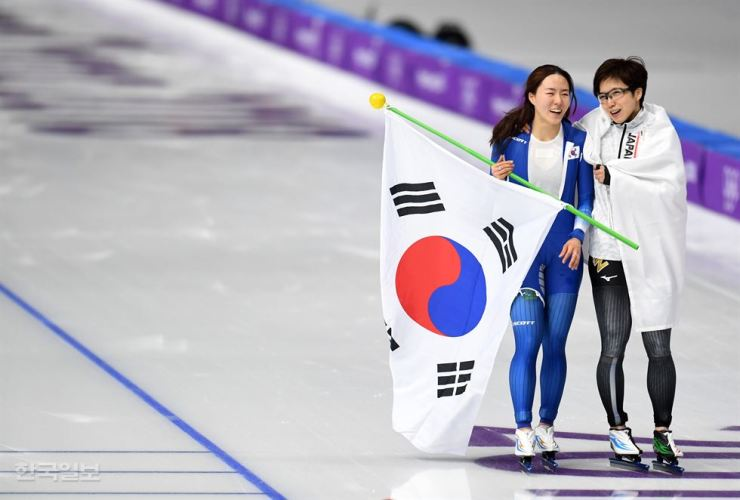Lee Sang-hwa of South Korea, left, and Nao Kodaira of Japan wear big smiles after the 500m speed skating finals at the Gangneung Oval Sunday. Kodaira claimed gold with an Olympic record of 37.28 seconds. Lee won silver clocking in at 37.33 seconds. / Korea Times photo by Kim Joo-young