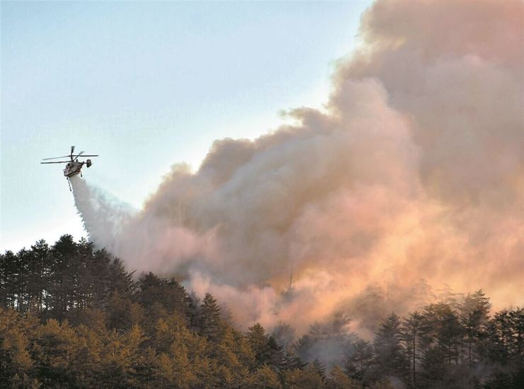 A helicopter flies over mountains in northern Samcheok, Gangwon Province, Monday, where fires broke out Sunday./Yonhap