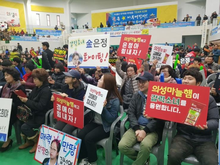 At Uiseong Gymnasium in Uiseong County, North Gyeongsang Province, Feb. 25, people cheer for South Korean women's curling team competing against Sweden in the final match. The county is where four of the five South Korean curlers are from. / Yonhap