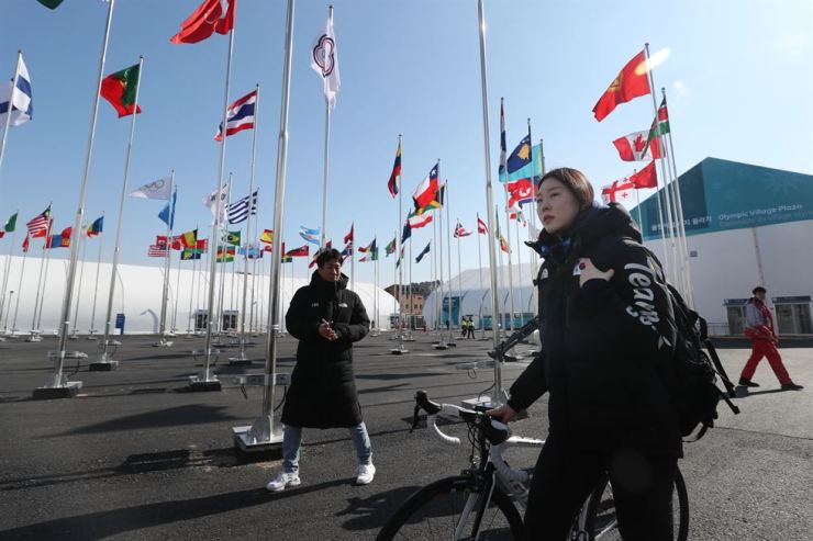 Speed skater Noh Seon-yeong of South Korea enters Gangneung Athletes Village through national flags raised to celebrate the PyeongChang Winter Olympic Games, Feb. 4. / Yonhap