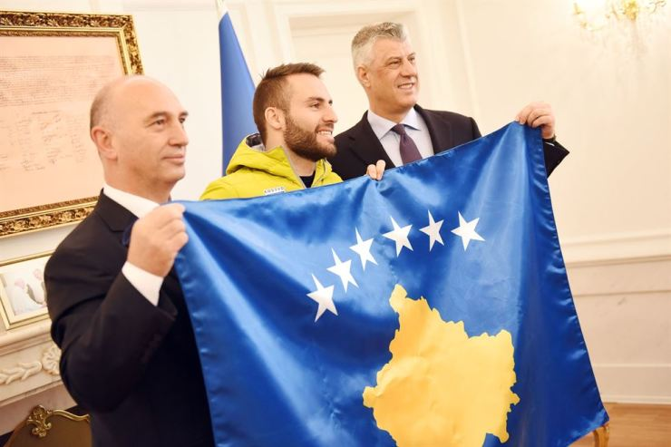 Kosovo President Hashim Thaci, right, holds the national flag of Kosovo with Albin Tahiri, center, the country's first Winter Olympian participating in the PyeongChang Games, during a ceremony in Kosovo, Feb. 5. / Courtesy of Kosovo Presidential Office