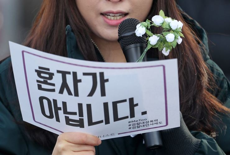 A protester reads texts during a rally demanding justice for public Prosecutor Seo Ji-hyun, who alleged she had been harassed by her senior supervisor, in front of the Daegu District Prosecutors' Office, Thursday. #MeToo is written in the back of the paper, with the Korean sentence saying 'You're are not alone.' / Yonhap