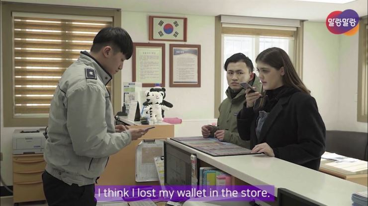 In a promotion film for 'Genie Talk,' foreigners use the translator/interpreter app at a police station. / Courtesy of Hancom