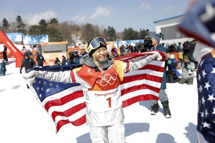 Korean-American snowboarding prodigy Chloe Kim holds up the American flag after winning gold in the women's halfpipe Feb 13. Korea Times photo by Shim Hyun-chul