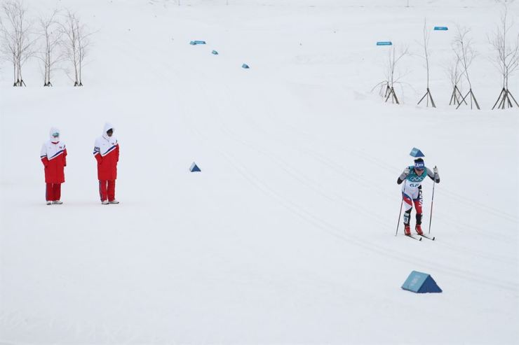 South Korea's Kim Eun-ho, right, skis during his PyeongChang Olympics men's cross-country 15km+15km skiathlon race at Alpensia Cross-Country Centre, Sunday, with two North Korean coaches rooting for Kim, who was far behind the main group. / Yonhap