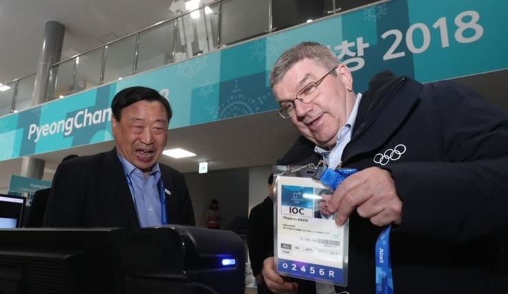 IOC President Thomas Bach, right, has his accreditation ID scanned to enter the 2018 PyeongChang Winter Games organizing committee headquarters. / Yonhap