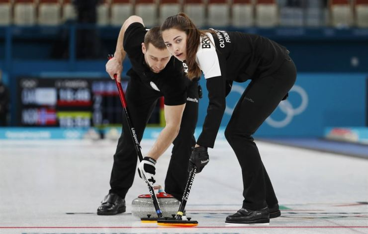 Russian curler Alexander Krushelnytsky, left, sweeps the ice along with his wife Anastasia Bryzgalova during the semifinals of the mixed doubles curling in Gangneung, Feb. 13. Krushelnytsky tested positive for a banned substance. / Reuters-Yonhap