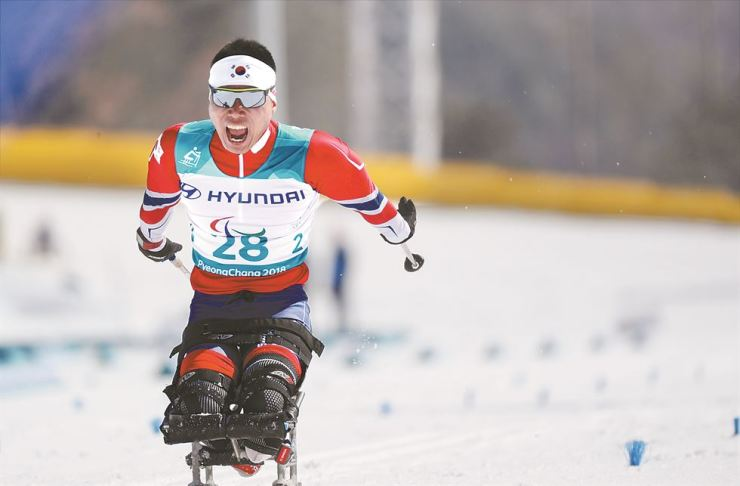 Nordic skier Sin Eui-hyun crosses the finish line in the men's 15-kilometer sitting cross-country race at the Alpensia Biathlon Center in the eastern county of PyeongChang on Sunday. / Yonhap