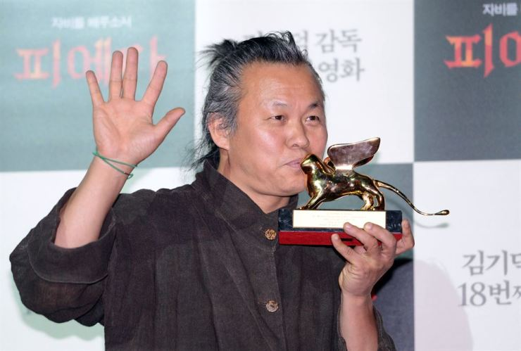 Kim Ki-duk kisses the Golden Lion Award of the 69th Venice International Film Festival at a press conference in the Megabox movie theater in central Seoul on Sept. 11, 2012. / Korea Times file