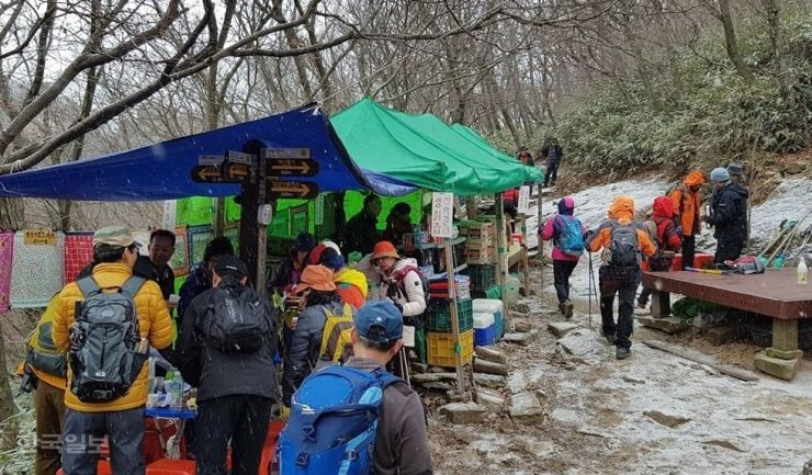 Trekkers at Daedunsan Provincial Park line up to buy liquor from vendors on Mt. Daedun. Provincial watchdogs have been reluctant to shut down the illegal traders, allowing the business to go on for years. / Korea Times file