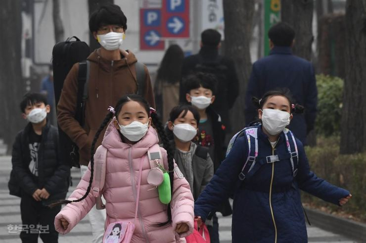 Students from Midong Elementary School in Seodaemun-gu, Seoul, head to their classrooms wearing masks on March 26 as air pollution and fog hit South Korea hard. / Korea Times file
