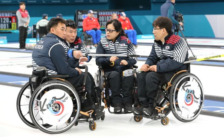 National wheelchair curling team members have a meeting in the middle of the game against Canada at the Gangneung Curling Center on Monday. South Korea won 7-5. / Yonhap