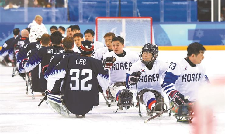 South Korean and U.S. sledge hockey players greet each other after their game at the Gangneung Hockey Center, Tuesday. The United States routed South Korea 10-0. / Yonhap