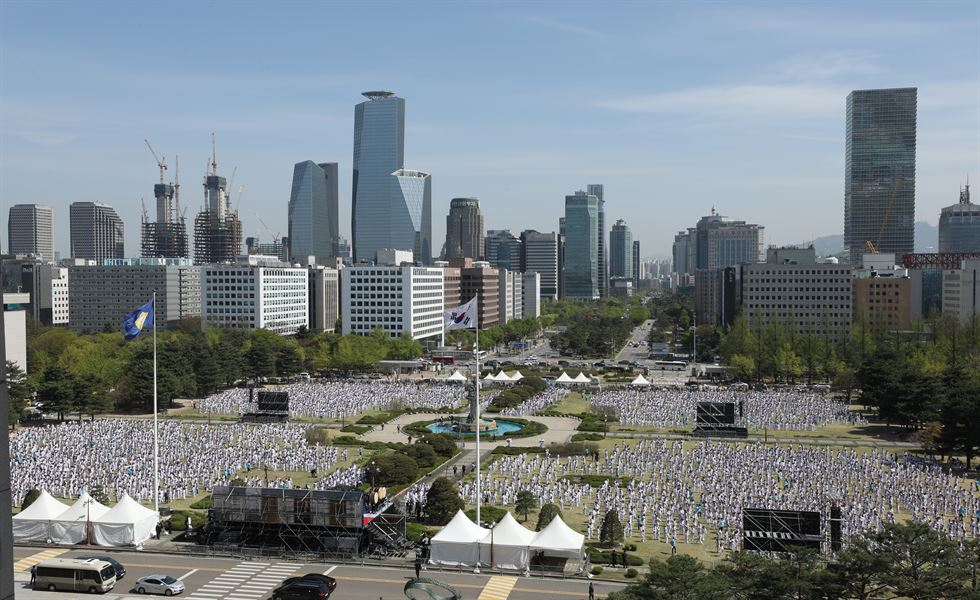 About 8,800 taekwondo martial artists perform poomsae in front of the National Assembly in Yeouido, Seoul, on April 21. Jets from the South Korean air force's 53rd Air Demonstration Group fly above. / Yonhap