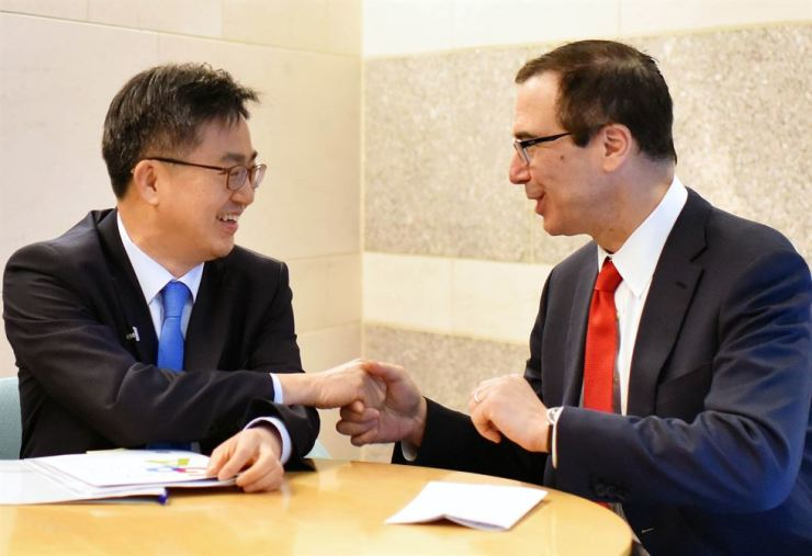 Strategy and Finance Minister Kim Dong-yeon, left, shakes hands with his U.S. counterpart Steven Mnuchin at a bilateral meeting in Washington, D.C., Saturday (local time). The meeting was on the sidelines of the G-20 finance ministers and central bank governors meeting. / Yonhap