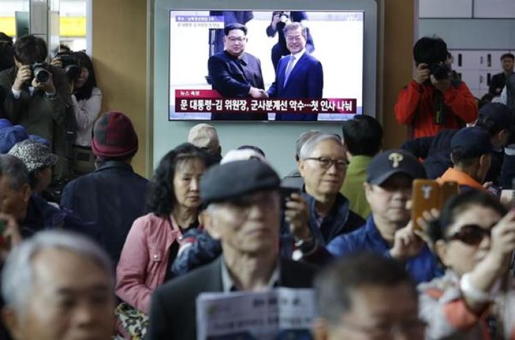 People at Seoul railway Station watch the live TV broadcast of the inter-Korean summit on Friday. / AP-Yonhap
