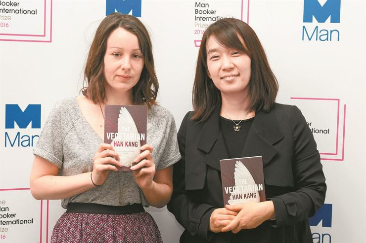 Han Kang, right, author of 'The Vegetarian,' and Deborah Smith, who translated the Korean novel into English, pose while holding the award-winning book in London in May 2016 after they won the 2016 Man Booker International Prize. The two have been nominated for the same award this year for Han Kang's 'The White Book,' along with 12 others. The winners will be announced in May amid new allegations that Smith's translation of 'The Vegetarian' was flawed. / Korea Times file