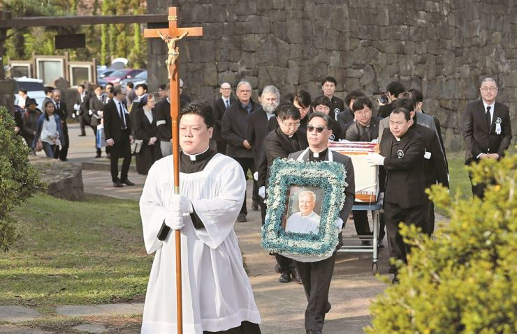 A man carrying a photo of the Rev. Patrick McGlinchey follows a cleric carrying a cross at St. Isidore Farm on Jeju Island during the Irish priest's funeral on Friday. Behind them are people who were pallbearers. McGlinchey died on April 23 while undergoing treatment for myocardial infarction and renal failure at a hospital on Jeju. / Yonhap