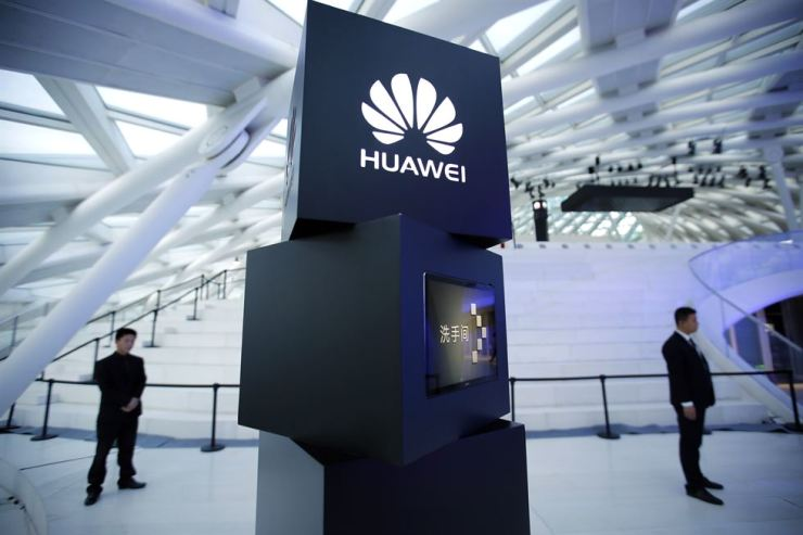 Security personnel stand near a pillar with the Huawei logo at a launch event for the Huawei MateBook in Beijing in May 26, 2016. Huawei Technology has a reputation for manufacturing high-quality network equipment at competitive prices, but Korean telecom firms are at a crossroads when it comes to decide on whether to select the Chinese equipment for their 5G network due to security concerns. / AP-Yonhap