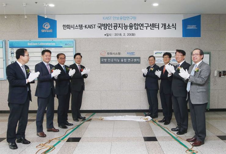 Hanwha Systems CEO Chang Si-kweon, fourth from left, and KAIST President Shin Sung-chul, fifth from left, applaud at the opening ceremony of the Research Center for the Convergence of National Defense and Artificial Intelligence in this Feb. 20 file photo. / Courtesy of Hanwha Systems