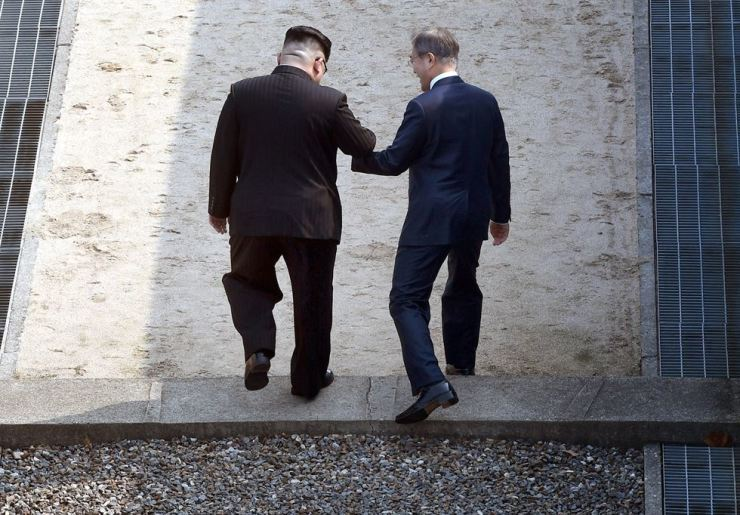 Kim and Moon, hand-in-hand, cross over the military demarcation line into the North, Friday. / Joint Press Corps
