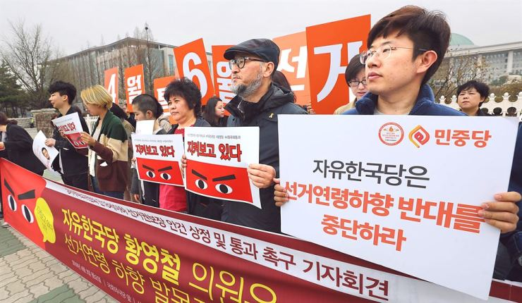 Members of a civic alliance for youth's human rights call for the main opposition Liberty Korea Party to stop opposing the move to lower the voting age from 19 to 18, during a rally in front of the National Assembly in Seoul, March 22. / Yonhap