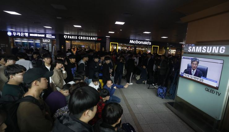 People in Seoul Station watch the judge reading the verdict on former President Park Geun-hye on television, Friday. /Korea Times photo by Shim Hyun-chul