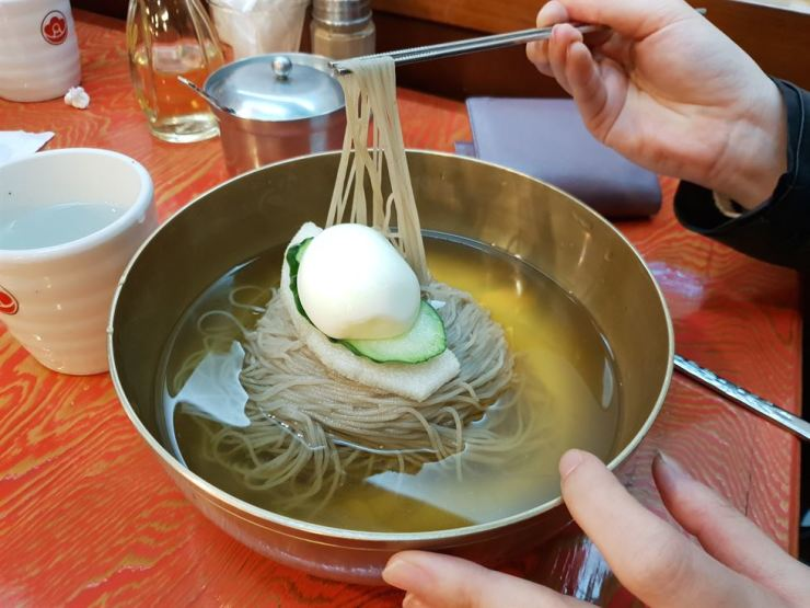 A Korea Times staff member tries Pyongyang naengmyeon at a restaurant in Jung-gu, central Seoul, Sunday. / Korea Times photo by Lee Suh-yoon