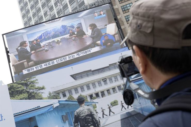 A citizen watches a live broadcast of the inter-Korean summit in front of Seoul City Hall, Friday. / Yonhap