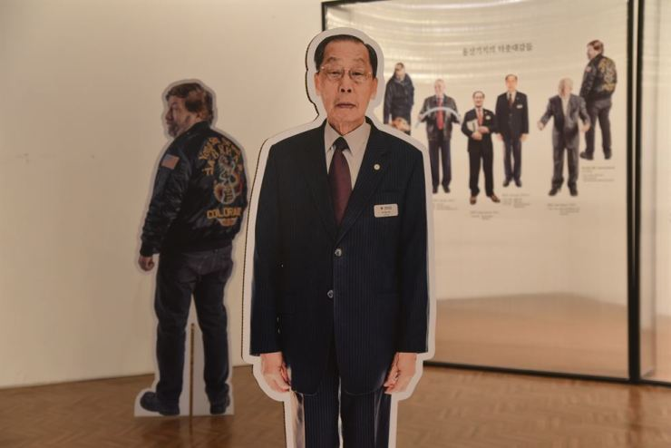 A full-size cardboard cutout of Yu In-su, who worked for over 35 years as a Korean civilian for the USFK, is on display at the 'Yongsan: The Unreachable Land' exhibit. Behind him is Charles Woodruff, librarian at Seoul American High School who worked as a CID clerk in Camp Coiner in the 1970s.