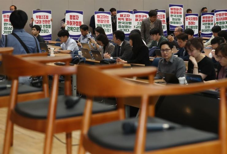 Seats for GM Korea senior executives are empty while members of GM Korea's irregular workers union chant slogans, as the press conference was canceled at a GM Korea plant in Incheon, Monday. / Yonhap