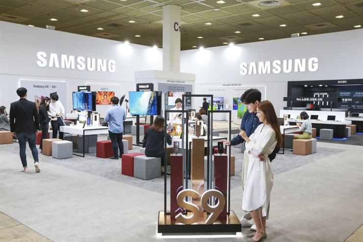 Visitors look around Samsung Electronics' booth displaying the firm's new flagship phone Galaxy S9 during the World IT Show 2018 that began Wednesday for a four-day run at COEX in southern Seoul. / Courtesy of Samsung Electronics