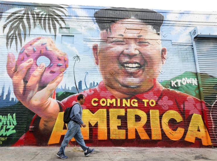 A mural depicting North Korean leader Kim Jong-un looms over a passerby near the Koreatown neighborhood in Los Angeles, Thursday. Earlier in the day, U.S. President Donald Trump canceled a planned summit with Kim Jong-un. / EPA