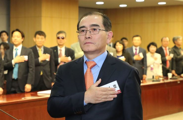 Thae Yong-ho, former North Korean diplomat who defected to the South in 2016, salutes the South Korean national flag while attending a forum at the National Assembly, Monday. / Yonhap