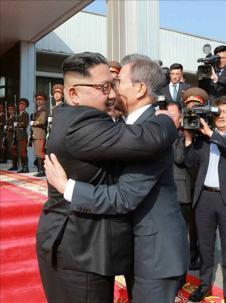 President Moon Jae-in and North Korean leader Kim Jong-un embrace after their surprise summit in the Panmunjeom truce village, Saturday. / Yonhap
